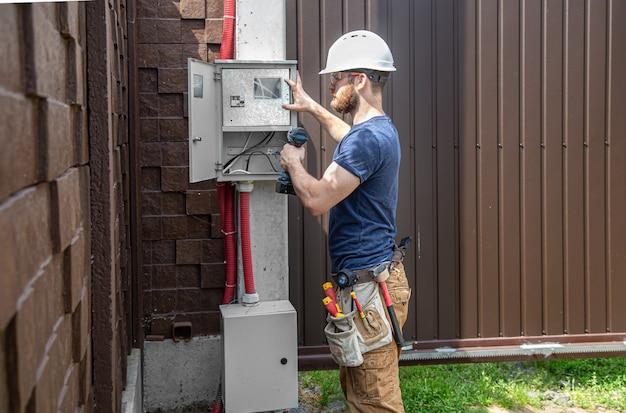 Elektricien-bouwer op het werk, onderzoekt de kabelverbinding in de elektrische leiding in de romp van een industrieel schakelbord. professioneel in overall met gereedschap voor elektriciens.