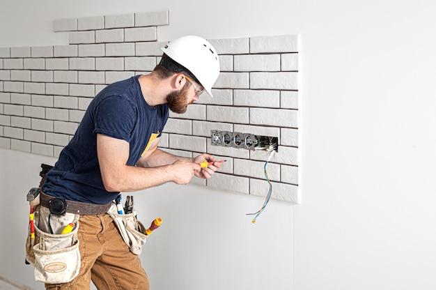 Elektricien bouwvakker met een baard in overall tijdens de installatie van stopcontacten. home renovatie concept.
