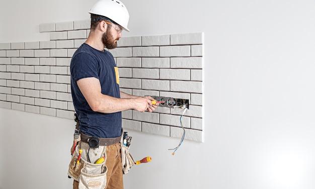 Elektricien bouwvakker met een baard in overall tijdens de installatie van stopcontacten. .