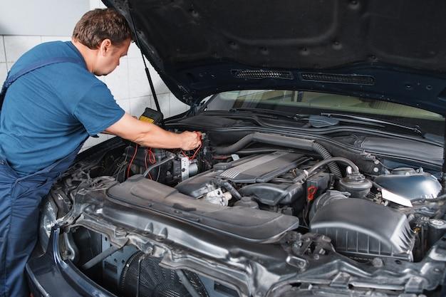 Elektricien die auto met multimeter test
