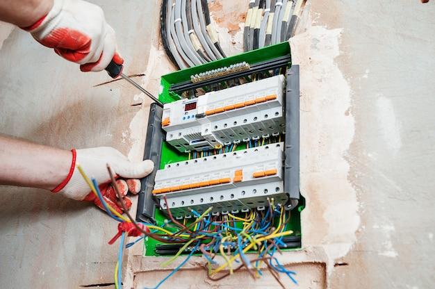 Elektricien die de zekeringen in de schakelkast installeert