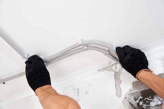 Elektricien die elektrische kabel aan de muur bevestigt