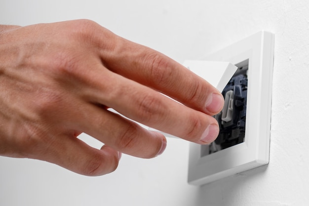 Elektricien die lichtschakelaar op muur installeert. detailopname