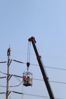 Elektricien die op hoogte werken door een hoogspanningsdraad aan te sluiten