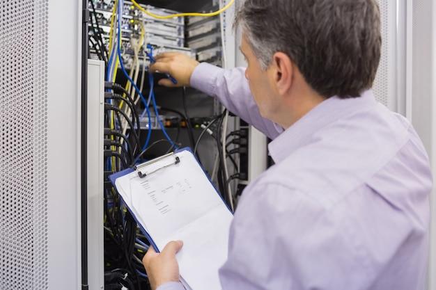 Elektricien die serveronderhoud met klembord doet