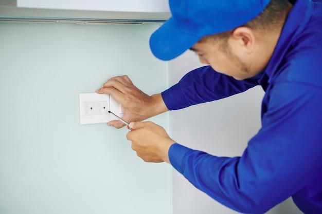 Elektricien die stopcontact installeert