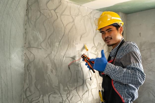 Elektricien die werkt met schakelaars en stopcontacten van een huishoudelijk elektrisch systeem.