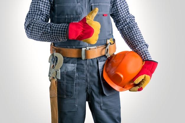 Elektricien duimen opdagen tegen grijs oppervlak. werknemer met veiligheidsgordel en helm voor persoonlijke beschermingsmiddelen.