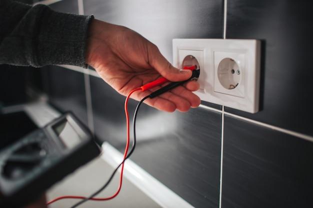 Elektricien, elektricien die nieuwe huidige contactdoos met schroevendraaier installeert.