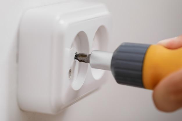 Elektricien elektrische aansluiting installeren op de muur met een schroevendraaier. detailopname
