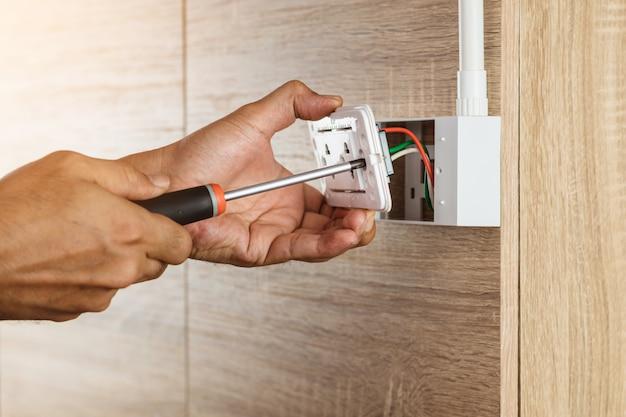 Elektricien gebruikt een schroevendraaier om een stopcontact te installeren in een plastic doos op een houten muur.
