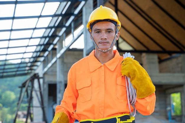 Elektricien in beschermende uniform werken op de bouwplaats.