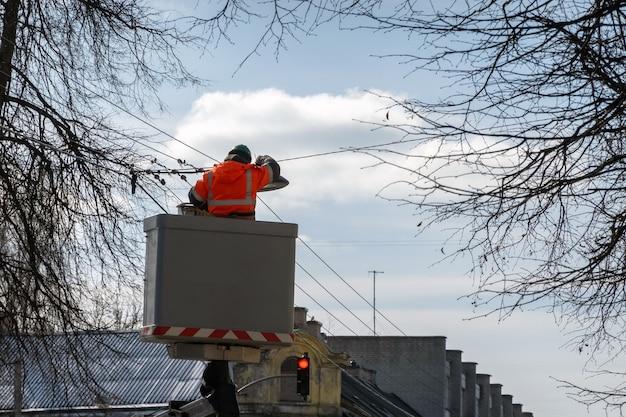 Elektricien in een liftplatform met beschermende werkkleding die openbare straatverlichting op een zonnige dag verandert.