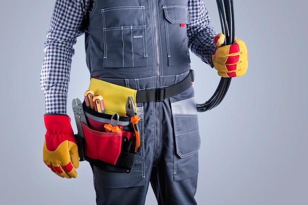Elektricien in uniform met draden op grijze ondergrond.