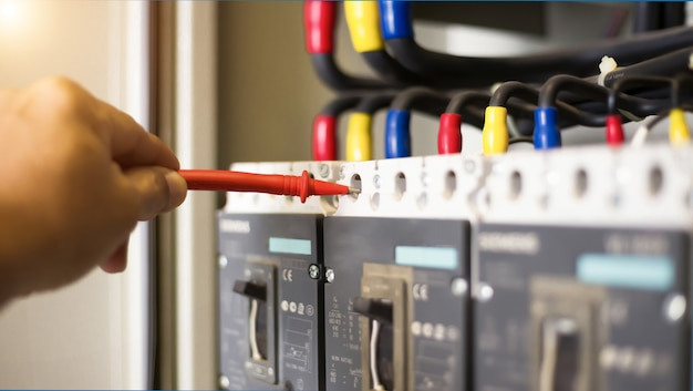 Elektricien ingenieur werk tester meten van spanning en stroom van elektrische stroomlijn in schakelkast controle.
