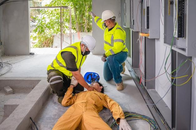 Elektricien kreeg bewusteloos een elektrische schok. veiligheidsteam cpr voor eerste hulp elektriciteitswerker verliest bij ongeval met elektrische schok op het werk ter plaatse. ongeval in de controlekamer van de fabriek.