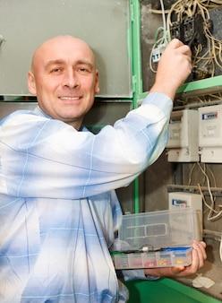 Elektricien man bedieningspersoneel installeren en monteren van nieuwe industriële bedrading op spanningspaneel