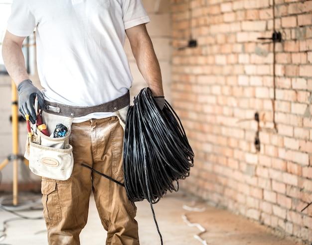 Elektricien met tools, werken op een bouwplaats