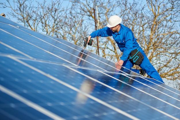 Elektricien montage zonnepaneel op dak van modern huis
