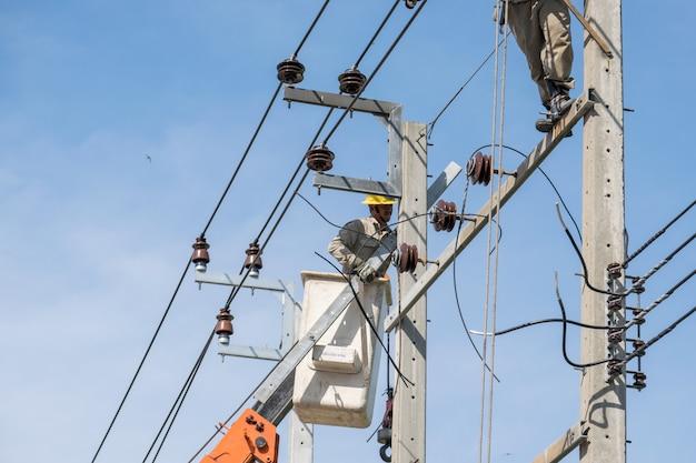 Elektricien op de liften die werken om hoogspanningsleidingen te repareren