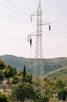 Elektricien repareert een elektrische ondersteuning van een hoogspanningslijn