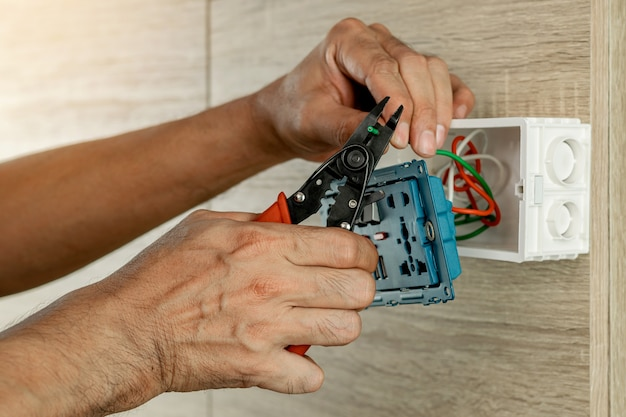 Elektricien stript elektrische draden in een plastic doos op een houten muur om het stopcontact te installeren.