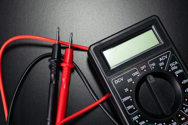 Elektricien tools op zwarte tafel, digitale multimeter op zwarte tafel
