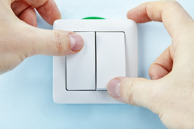 Elektricien zet nieuwe europese standaarddrukknop aan of uit.