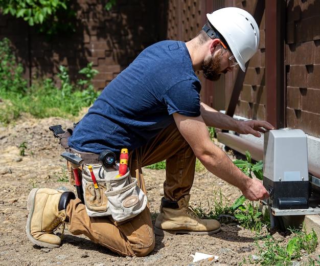 Elektricienbouwer aan het werk, die het industriële schakelbord van de romp onderhoudt. professioneel in overall met gereedschap voor elektriciens.