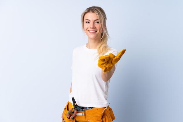 Elektricienvrouw over geïsoleerd blauw handenschudden na veel