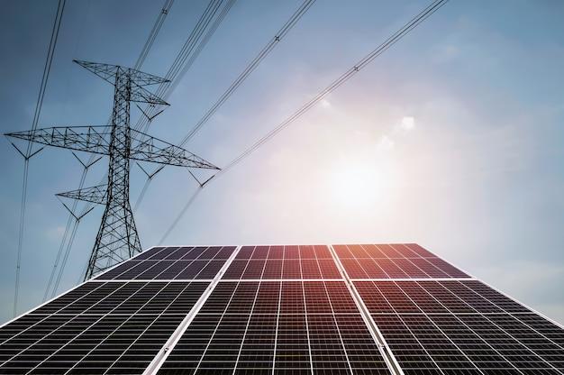 Elektriciteit in de natuur. schone energieconcept. zonnepaneel met turbine en torenhoogspanning