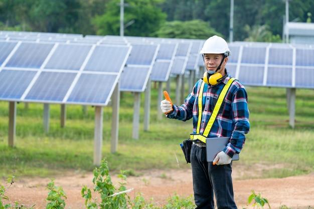 Elektriciteit zonne-energie engineering, ingenieur controle zonnepaneel in routine werking op zonne-energiecentrale.