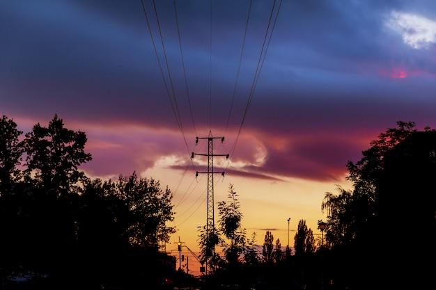 Elektriciteitslijnen afgetekend door hemel bij zonsondergang.