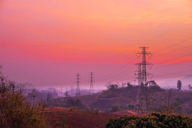 Elektriciteitspalen en landschap in de avond bij zonsondergang