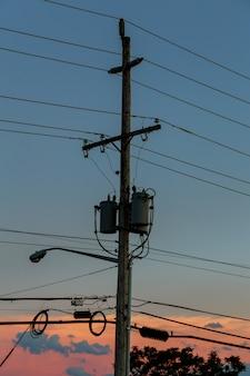 Elektriciteitspolen met zonsondergang, silhouet