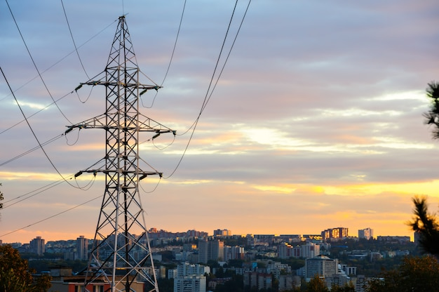 Elektriciteitspylonen en machtslijnensilhouetten bij een bewolkte zonsondergang.