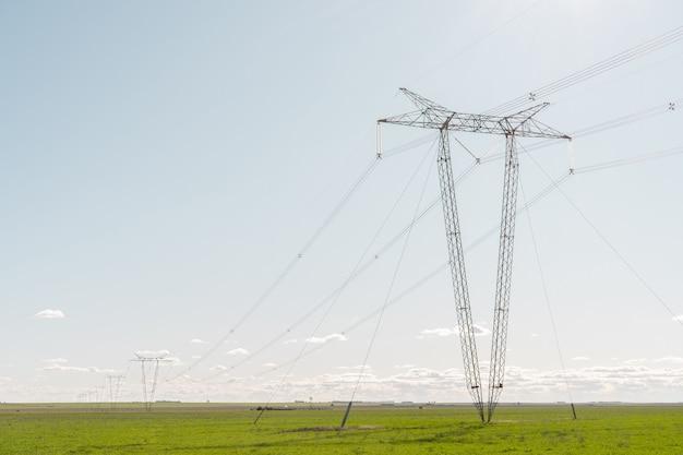 Elektriciteitstorens op een rij midden in een landbouwveld met heldere lucht
