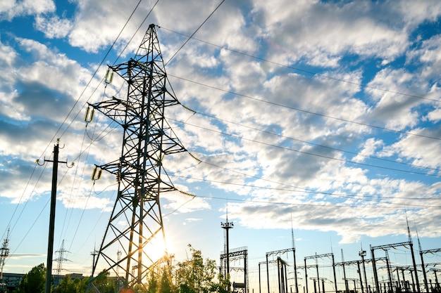 Elektrisch onderstation met hoogspanningsleidingen bij zonsondergang