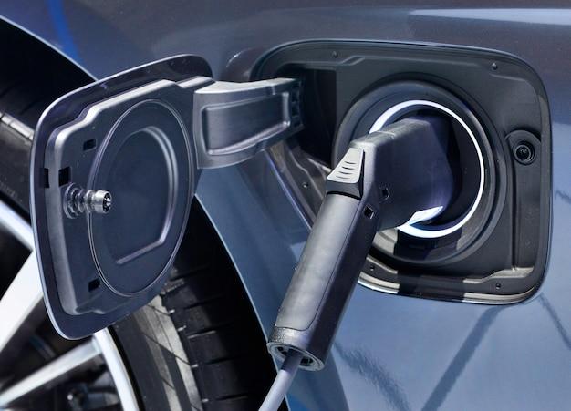 Elektrisch voertuig opladen in station met voeding aangesloten op een elektrische auto die wordt opgeladen.