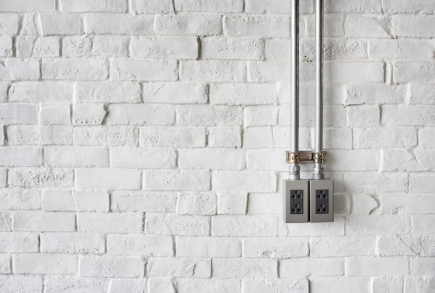 Elektrische aansluiting op een witte geschilderde bakstenen muur