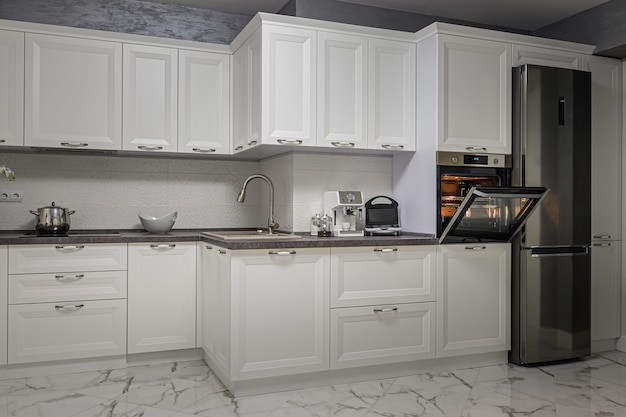 Elektrische apparaten in minimalistische witte keuken interieur