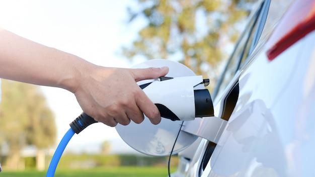 Elektrische auto of ev laadt op station. man gebruiken witte stroomkabel en stekker