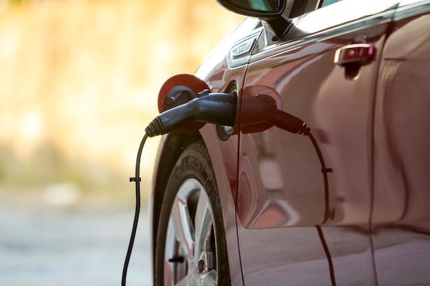 Elektrische auto wordt opgeladen op heldere zonnige straat.