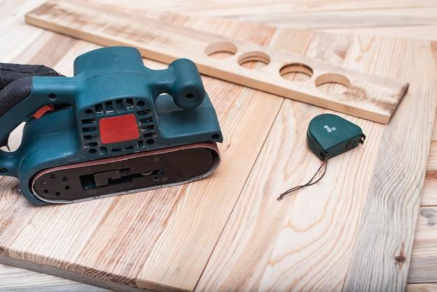 Elektrische bandschuurmachine, meetlint en werkstuk liggend op een lichtbruine houten tafel. houtbewerking, schuurmachine. detailopname