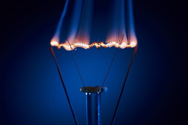 Elektrische bollamp met een brandende spiraal op een zwarte achtergrond