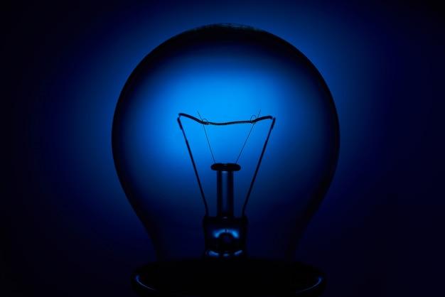 Elektrische bollamp met een spiraal op een blauwe achtergrond