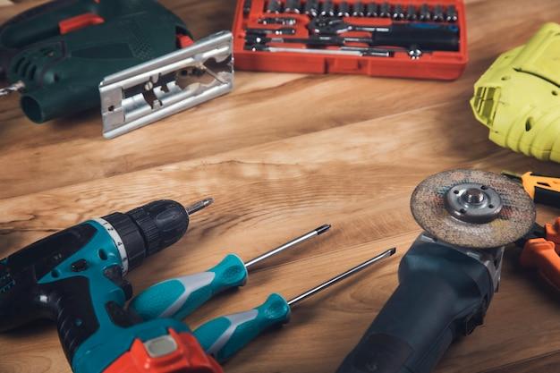 Elektrische boor en architectonische hulpmiddelen op houten tafel