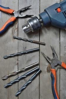 Elektrische boormachine en gereedschappen voor het werken op een houten oppervlak. bovenaanzicht.