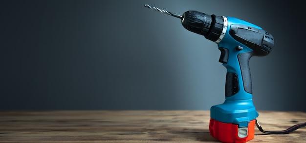 Elektrische boormachine op een houten tafel met een donkere achtergrond