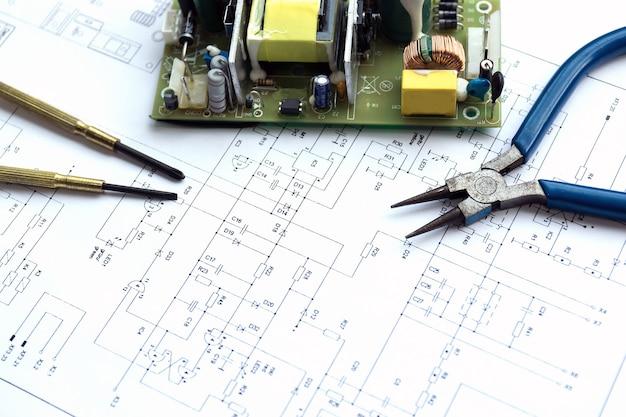 Elektrische componenten en precisiegereedschap liggend op constructietekening van elektronica